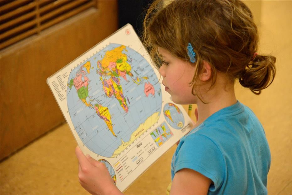 Young girl looking at world map