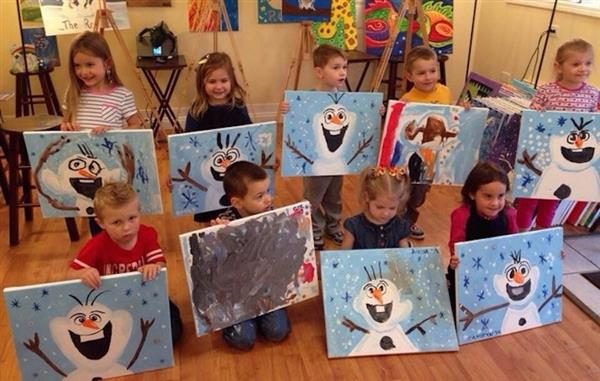 children holding their paintings
