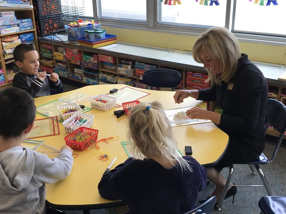 Board of Education President sitting at a table with kindergarten students