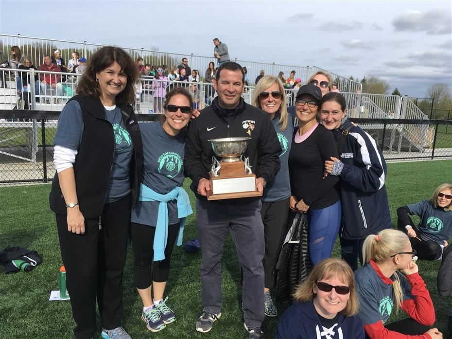 Superintendent Michael Pero holding a trophy and others on a kickball field