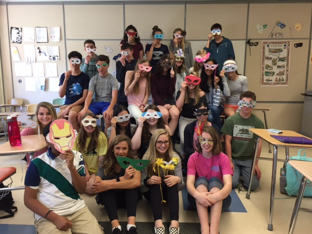 Honors 9 students holding homemade masquerade masks