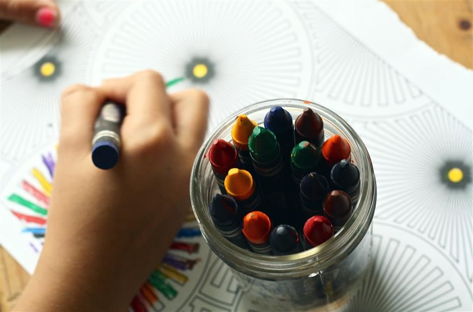 child coloring with a crayon next to a cup filled with crayons