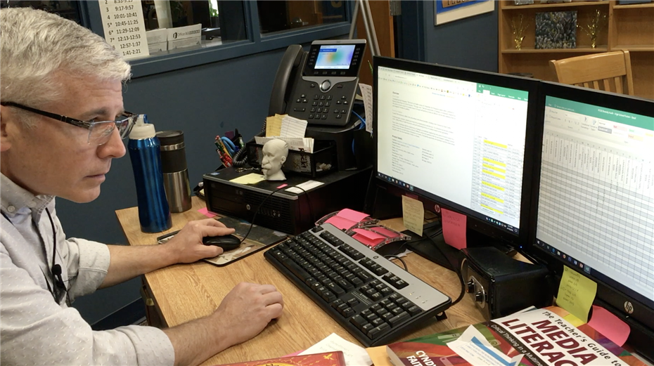 Library Media Specialist, Brian Regan, working on the library diversity audit.
