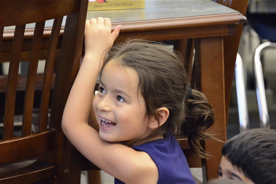 Elementary student smiling behind a chair